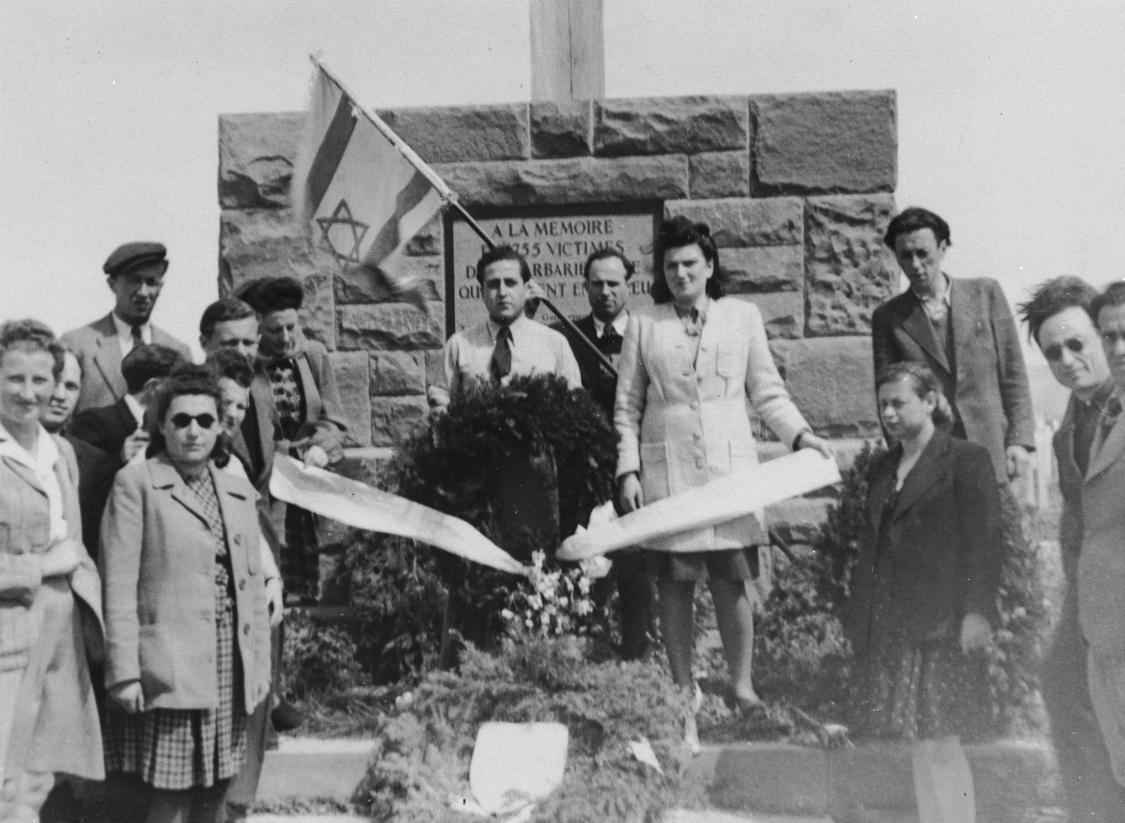 Jewish survivors lay a wreath at a monument to the victims of the Dautmergen subcamp of Natzweiler on the first anniversary of the liberation.  Among those pictured is Kiwa Dajches (in center group on the left).