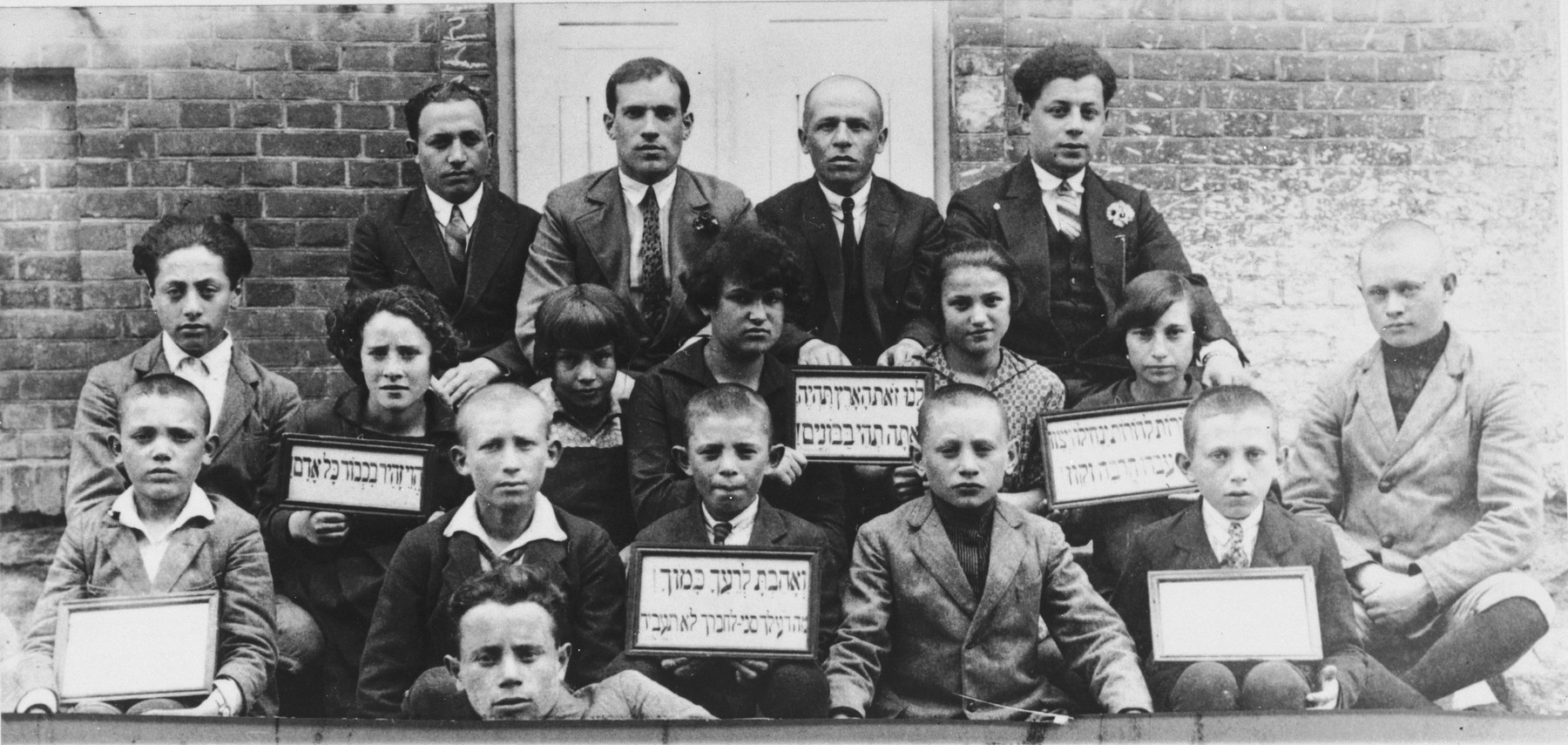 Group portrait of students and teachers at the Hebrew language Tarbut school in Grodek.    The children hold Hebrew signs with mottos from the sayings of the sages.   Among those pictured is Ralph Denishevsky (the donor's father, back row, first from the left).