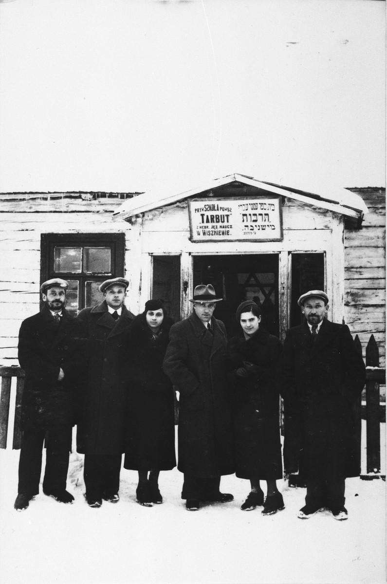 Six teachers from the Hebrew language Tarbut elementary school in Wiszniew pose outside in the snow in front of their school building.    Among those pictured is Ralph Denishevsky (third from the right).