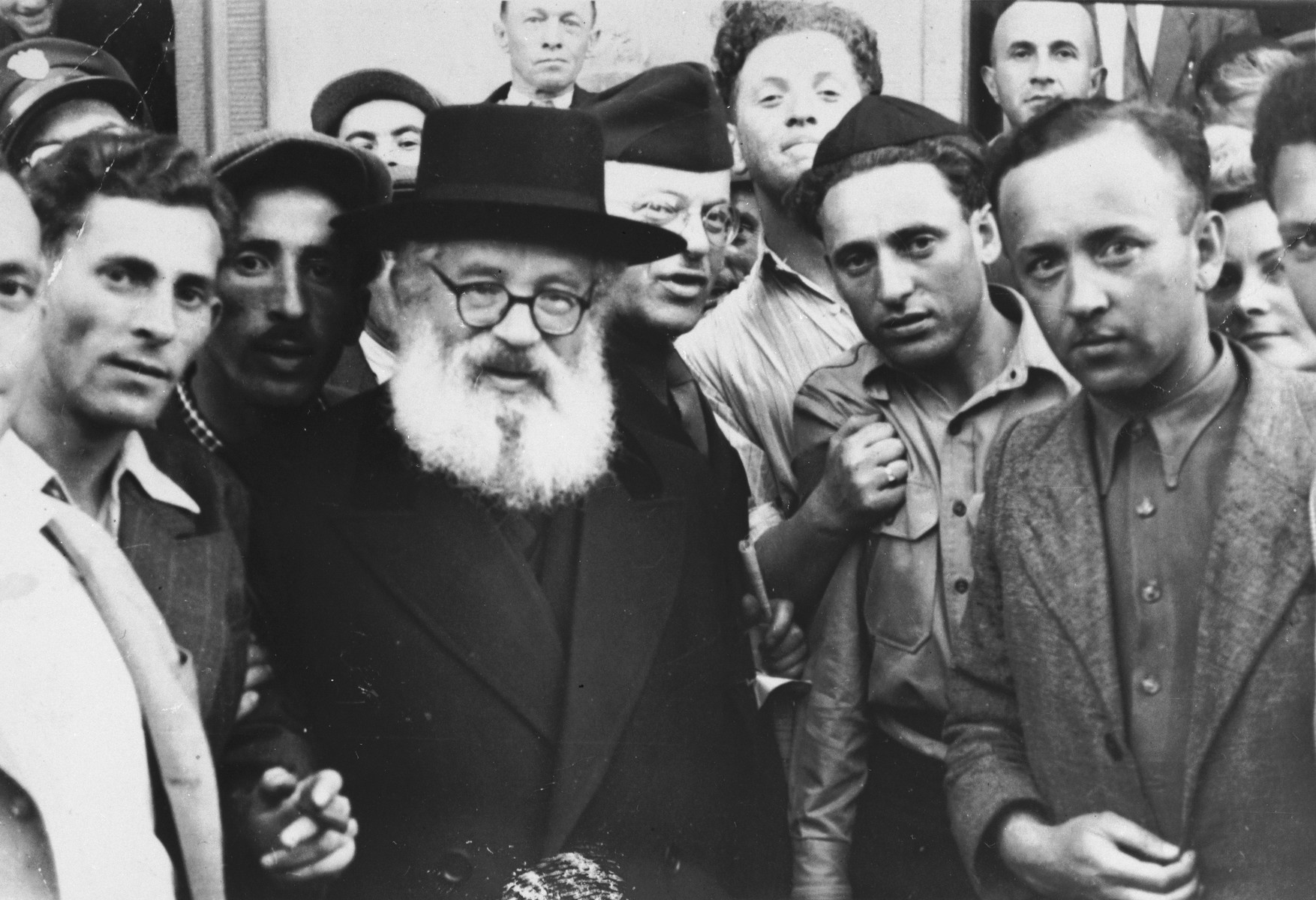 Ashkenazi Chief Rabbi of Palestine, Isaac Herzog, poses with Jewish DPs at the Lampertheim displaced persons camp during an official visit.  Izak Lachter is pictured wearing a skull cap next to Rabbi Herzog.  In the foreground at the right is Dr. Shmarholtz.