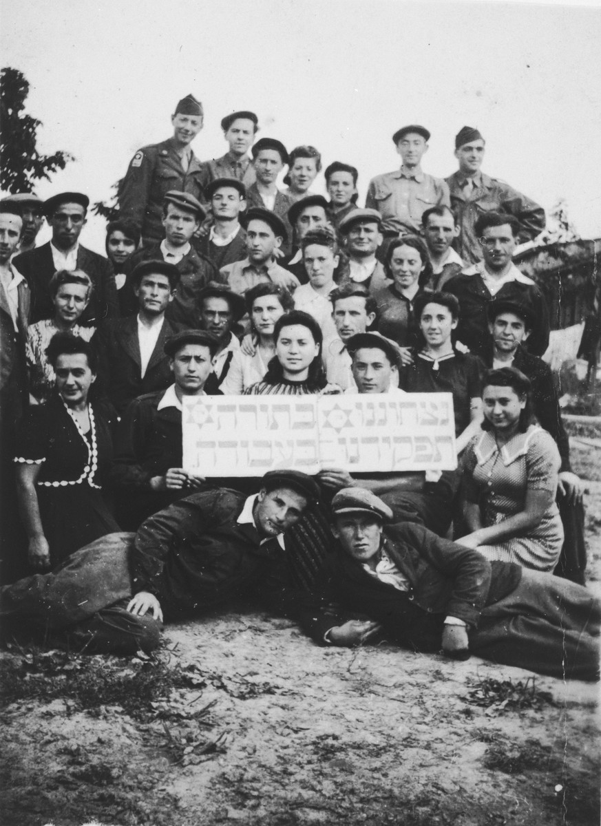 "Group portrait of members of the Mizrachi religious Zionist youth movement in the Ziegenhain displaced persons' camp holding a sign that reads, ""Our eternity is in Torah, our task is in work.""  Two American Jewish soldiers who assisted the group pose with them in the back row."