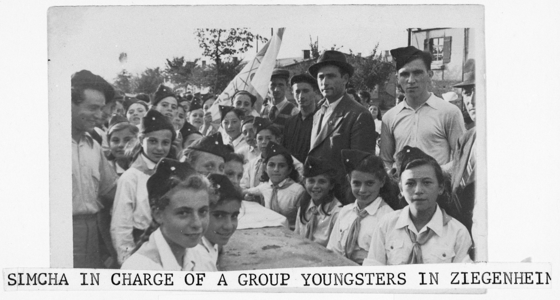 Children in the Ziegenhain displaced persons camp sit outside around a table in their new youth movement uniforms.  Posing with them are their two instructors, Simcha Langzam and Abraham Lomp.