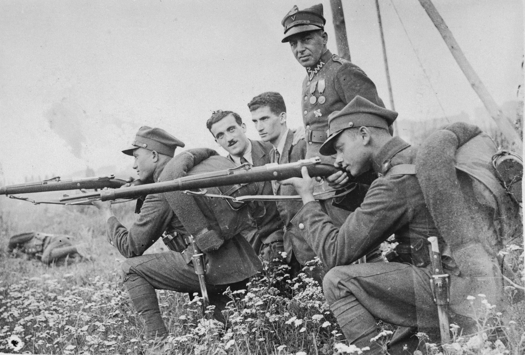 Jewish soldiers in the Polish army practice shooting.    The donor's husband, Majer Rozental, and his brother Nissan, are pictured in civilian dress in the center.  Majer (the brother on the left) survived the war by fleeing to the Soviet Union.  Nissan perished.