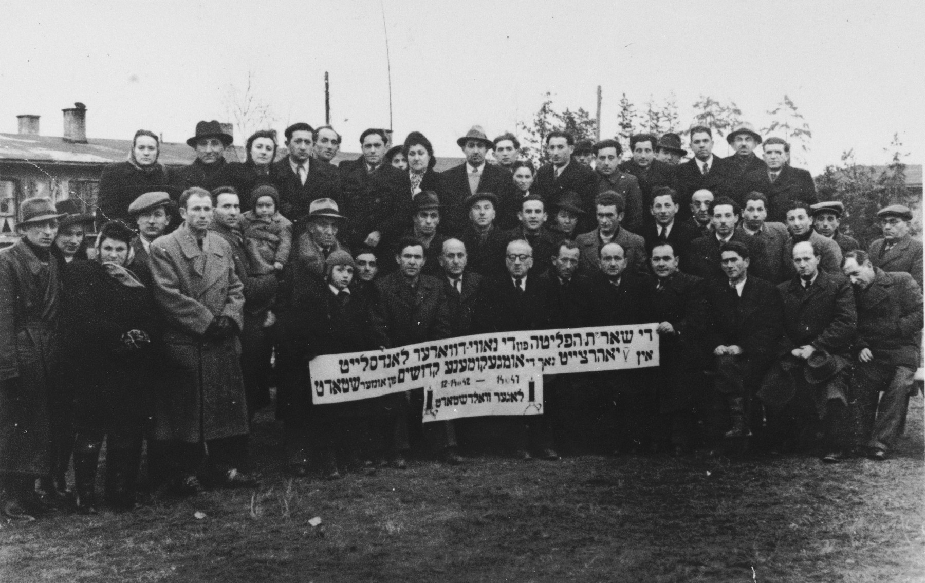 Group portrait of survivors at a commemoration of the destruction of the Jewish community of Nowy Dwor by the Nazis.  The commemoration took place at the Pocking displaced persons camp.  Pictured in the first row, fifth from the right is Iser Knecht.