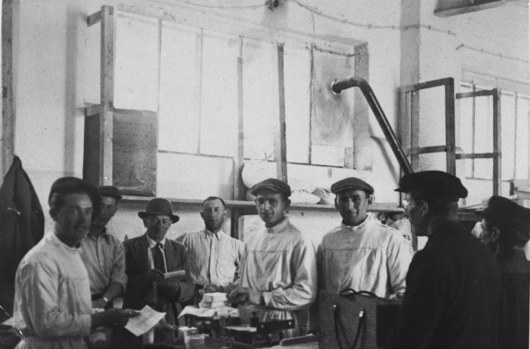 DPs working in food distribution at the Ziegenhain displaced persons' camp pose in a warehouse.  Second from the right is Shlomo Kleimann.