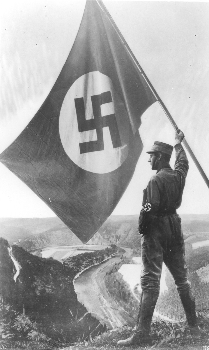 Picture postcard showing a member of the SA waving a large Nazi flag while standing on a mountain ridge overlooking a valley.  The postcard was produced by the Julius Schleicher Postkarten Verlag in Leisnig.