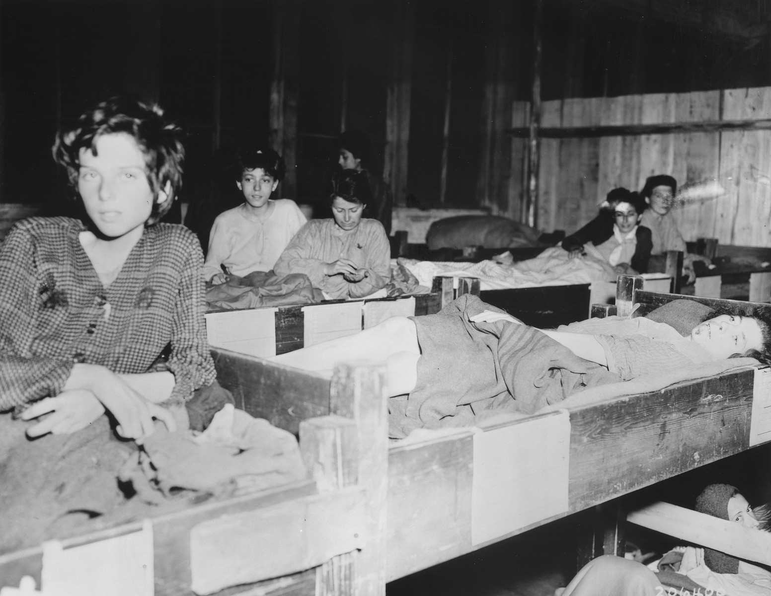 Female survivors of the Mauthausen concentration camp lie in wooden bunks in the hospital barracks.