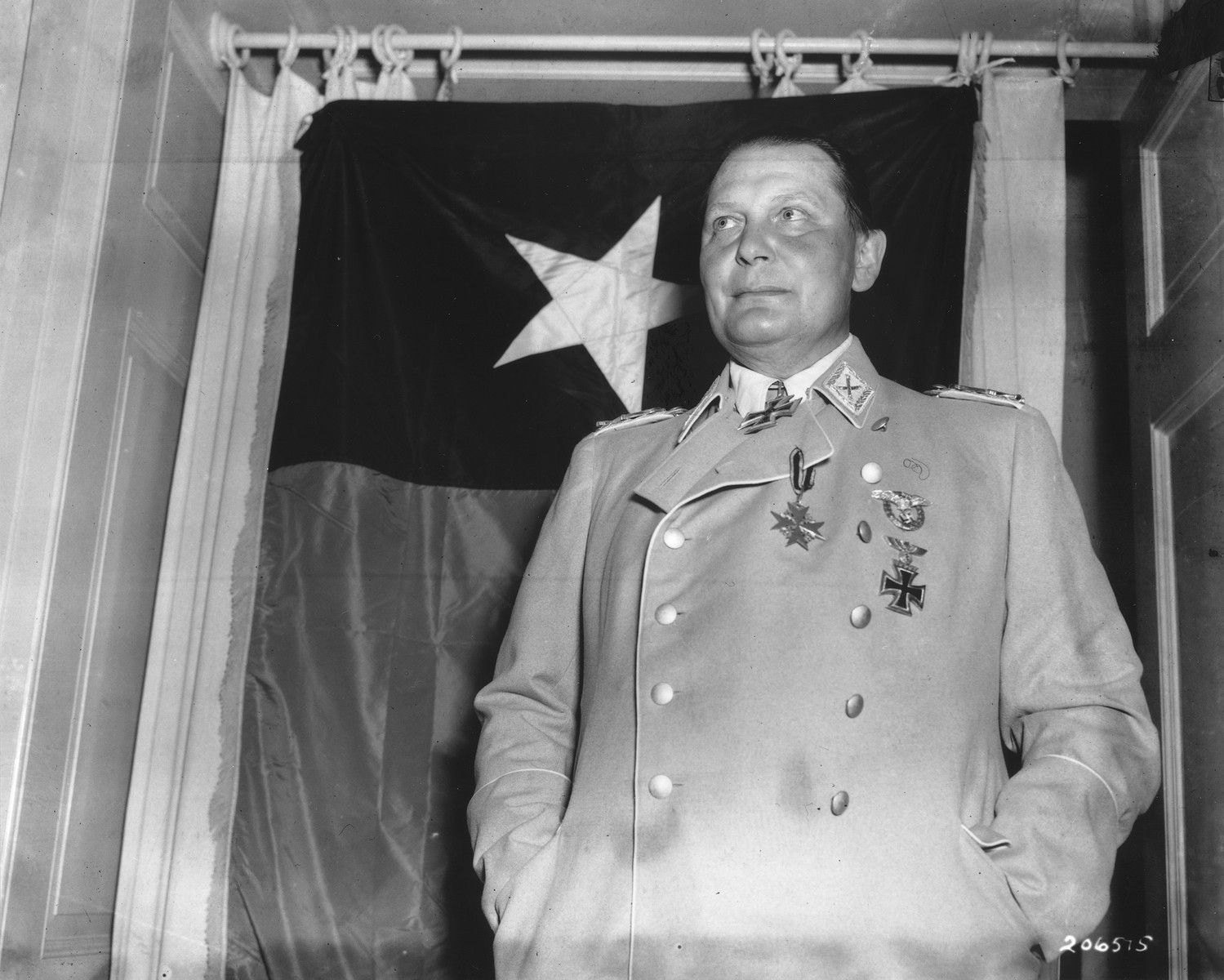 Reich Air Marshal Hermann Goering poses in front of the flag of the U.S. 36th Division at a castle near Kitzbuehel, Austria.  Goering was captured after being held prisoner by the SS at Berchtesgaden.  Hitler issued orders for his execution.