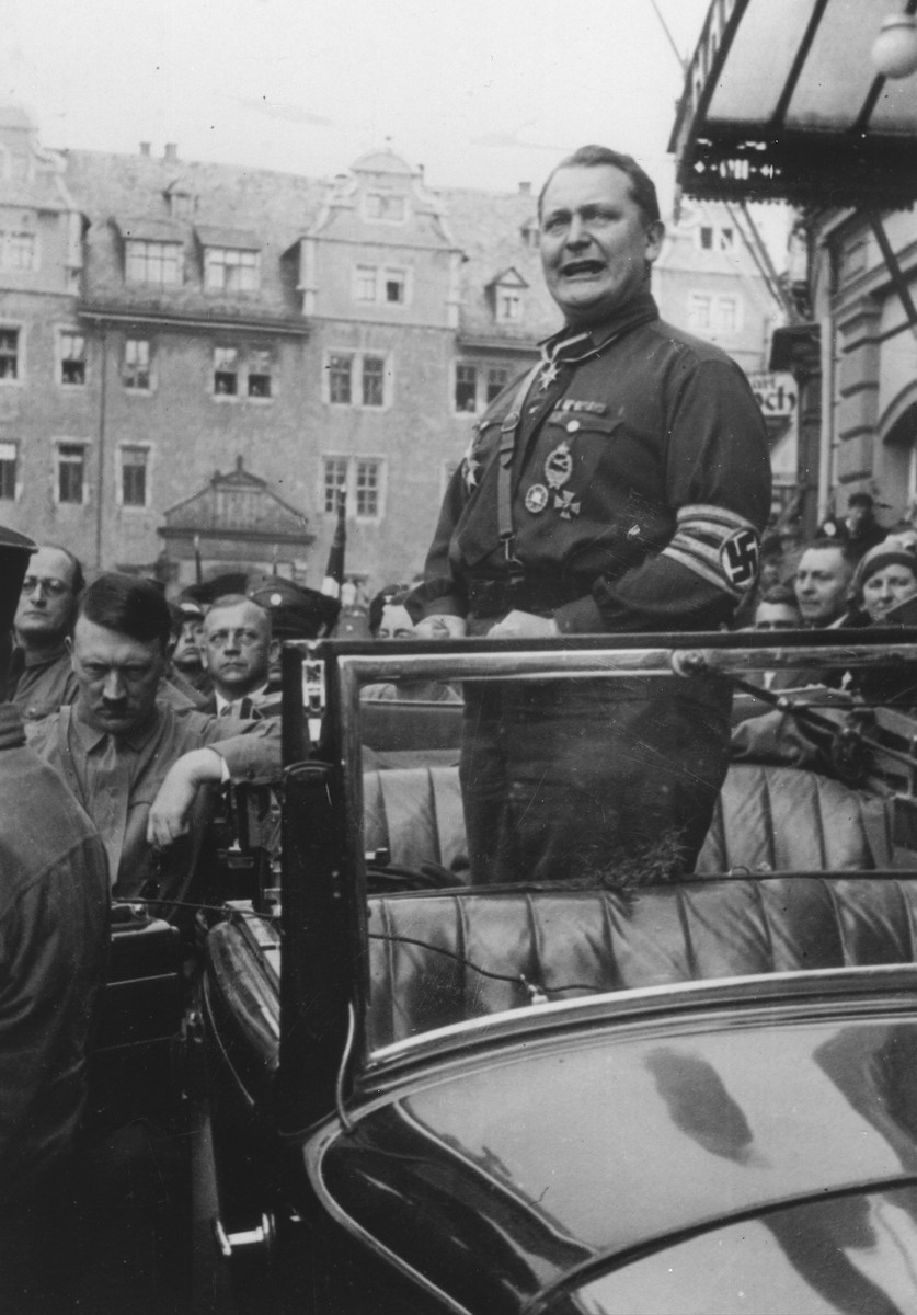 Hermann Goering delivers a speech while standing in an open car at the Gau Parteitag [District Party Day] rally in Weimar.  Adolf Hitler stands outside the car.