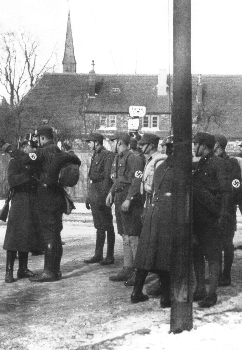 German police [Schutzpolizei] who are posted at the Berlin city line search SA men for weapons before allowing them to proceed to a rally in the capital.