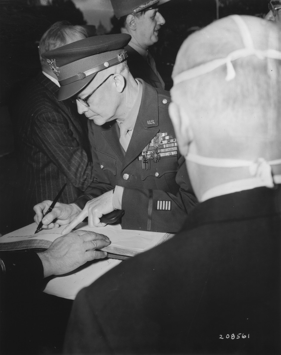 General Dwight D. Eisenhower signs the register at the tomb of the unknown soldier after a ceremony at the Arc de Triomphe, in which he was presented the Medal of Liberation by General Charles de Gaulle.
