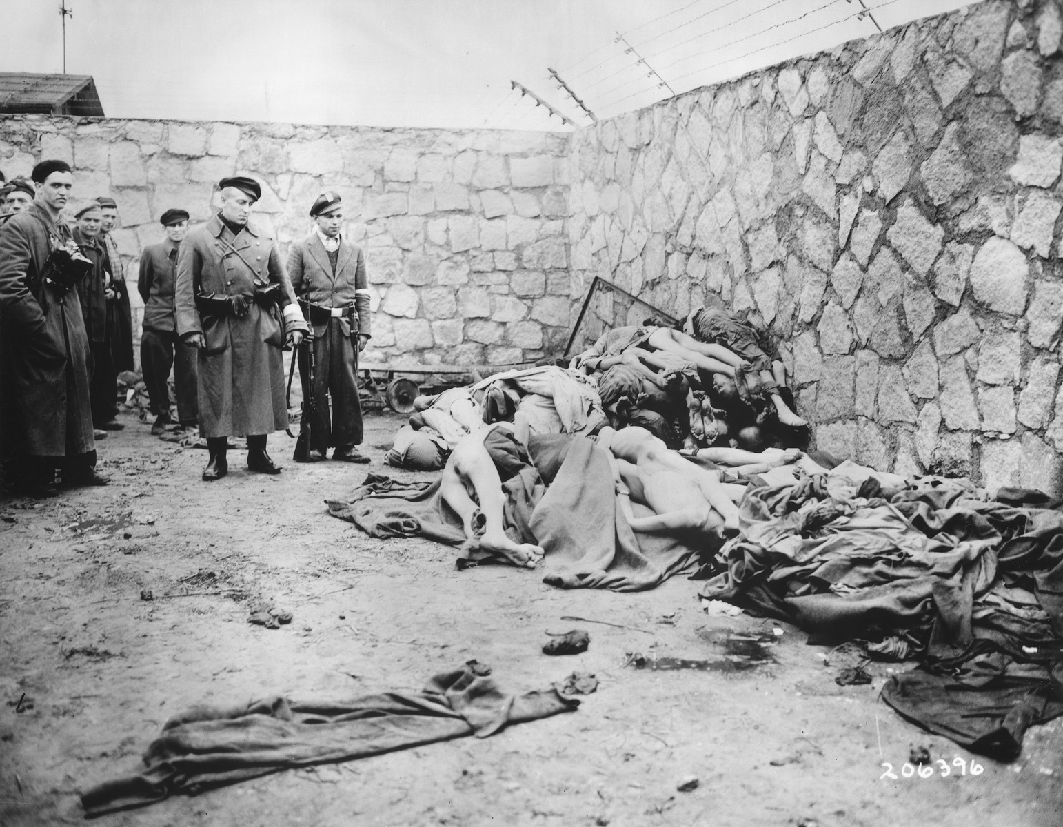 Photographer Francisco Boix and other survivors view a pile of corpses lying among abandoned blankets and clothing in front of a stone wall in the Mauthausen concentration camp.