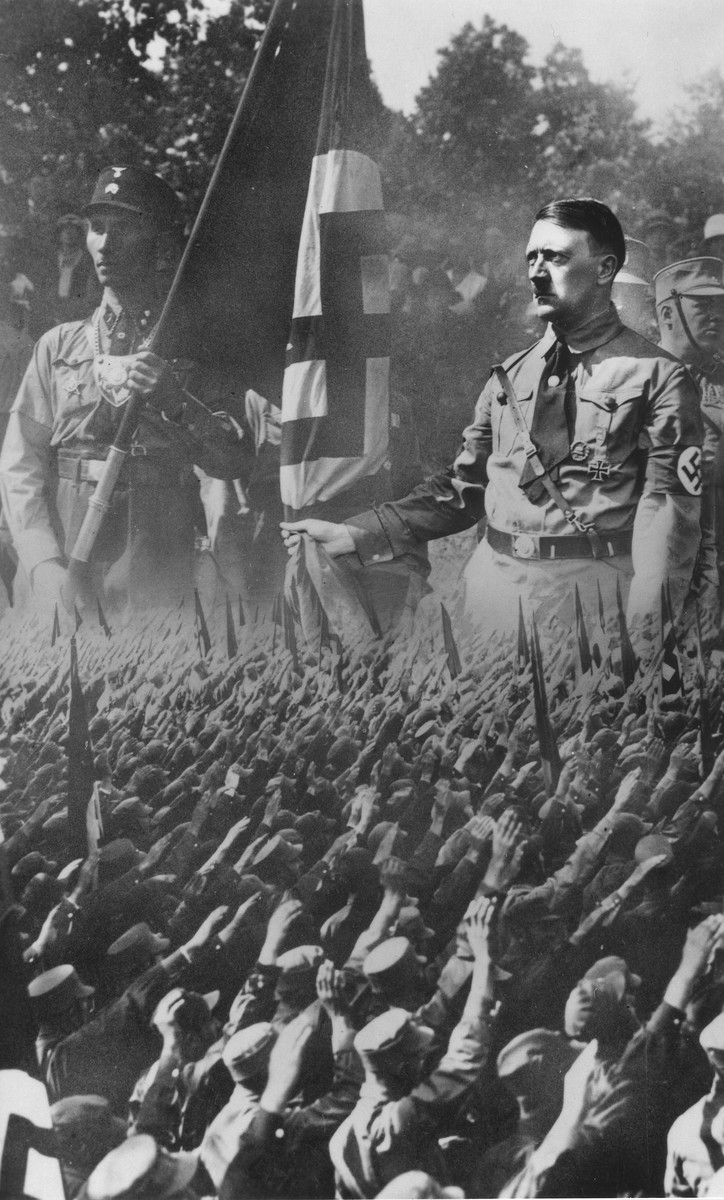 Picture postcard showing a crowd of saluting Germans superimposed on an enlarged image of Hitler and a Nazi stormtrooper.
