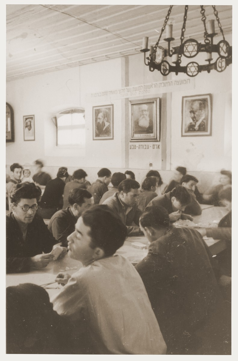 "Members of Kibbutz Nili hachshara (Zionist collective) in Pleikershof, Germany, sit around tables in the dining hall.  On the wall are photographs of Herzl, Weizman and A.D. Gordon and the Hebrew motto, ""Man-Work-Nature."""