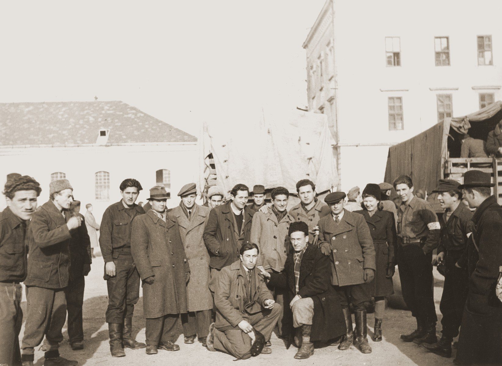 Group portrait of Jewish DPs who are about to leave Enns.  Bricha guide, George Birman is fifth from the left.
