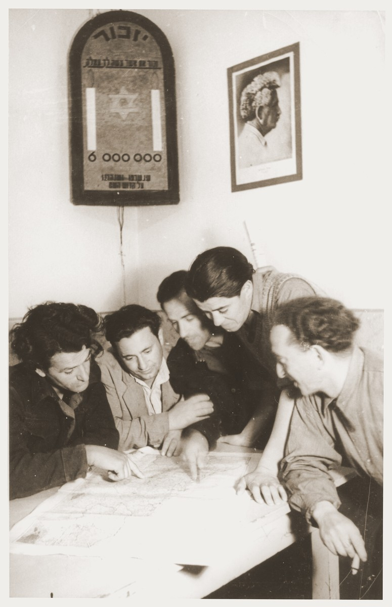 Members of the Kibbutz Nili hachshara (Zionist collective) in Pleikershof, Germany, study a map of Palestine beneath a wall plaque memorializing the six million killed in the Holocaust and a photograph of labor Zionist leader, Berl Katznelson.