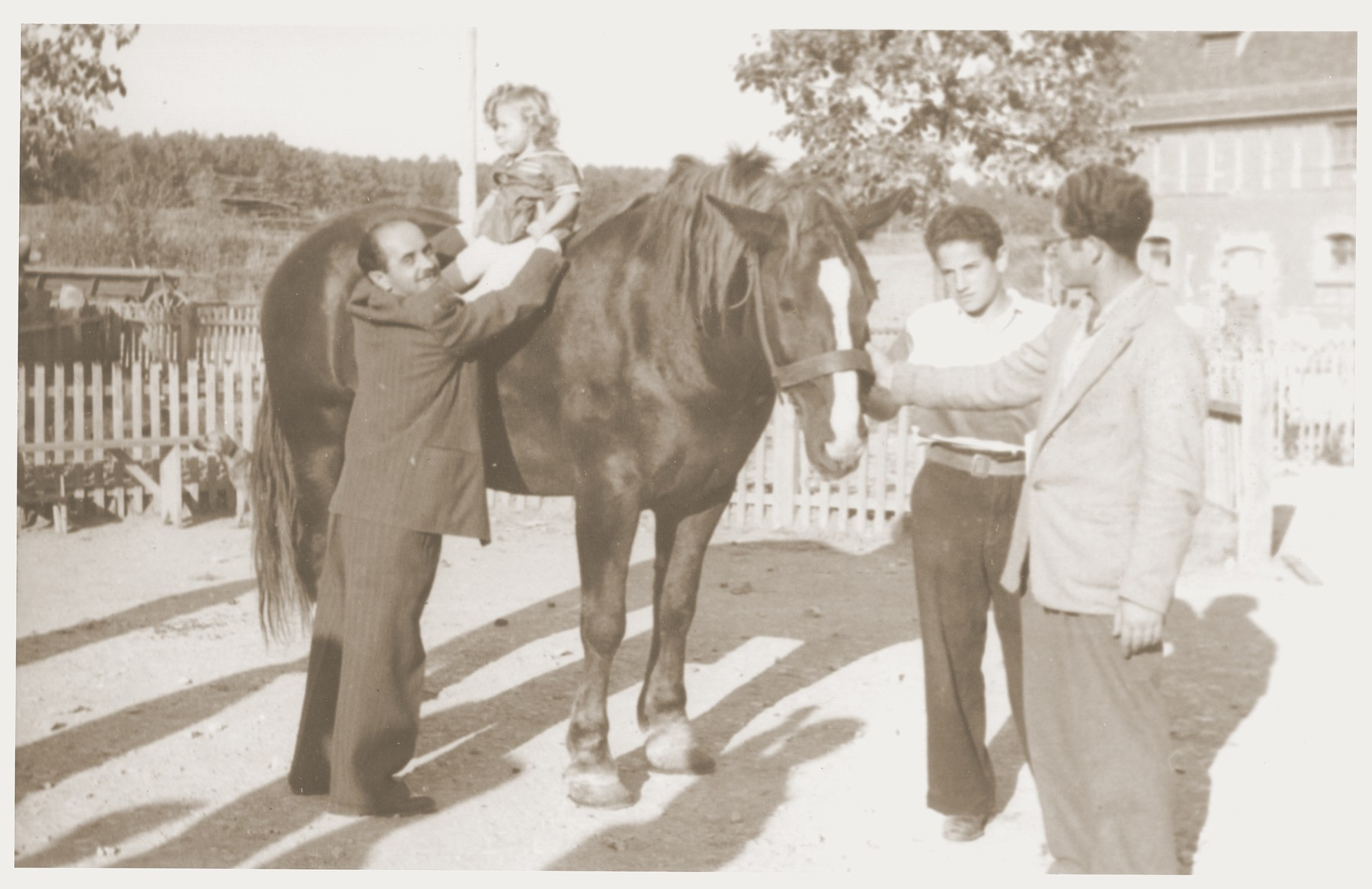 Noach Miedzinski lifts his daughter, Nili, onto one of the horses at the Kibbutz Nili hachshara (Zionist collective) in Pleikershof, Germany.