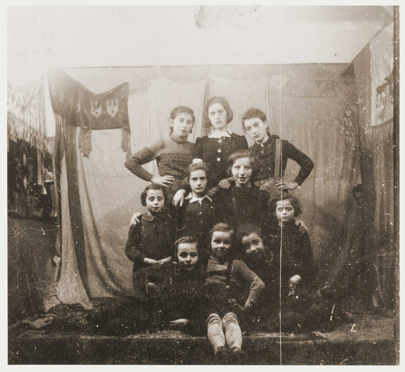 Group portrait of Jewish children in front of a stage set at a Purim celebration in the Zabno ghetto.