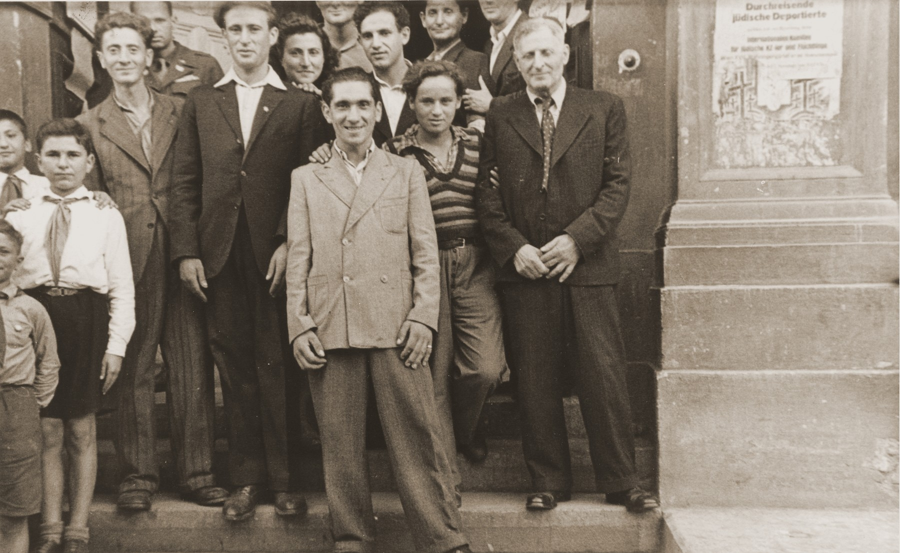 Jewish DPs stand on the steps of the Rothschild Hospital to greet the delegation from the United Nations Special Commission on Palestine.  Abel Birman, father of the donor, stands on the far right.  .   Between July 1945 and May 1948 approximately 250,000 Jewish holocaust survivors fled from eastern Europe to displaced persons' camps in Germany, Austria and Italy, in what was the largest organized, illegal, mass movement in modern times.  Both the movement and the organization that directed its flow are known by the name Bricha [flight]. The Bricha was born when groups of Zionist partisan survivors from eastern Europe, who had attempted unsuccessfully to reach Palestine via Romania, made contact with Jewish Brigade troops stationed in Italy.  The soldiers offered them the possibility (although limited and illegal) for reaching Palestine via Italy.  Together they established the Bricha in Poland, an organization that quickly came under the direction of Haganah (Jewish underground) emissaries from Palestine.  Bricha guides led groups of survivors on specially laid out routes from Poland to Italy and Germany.  The transit expenses were covered by the American Jewish Joint Distribution Committee, which also provided food and shelter along the routes.  Generally, the Soviet authorities turned a blind eye to the illegal migration, the British were hostile, and the Americans were accepting, because they could not use force to stop the flow.  The largest wave of the Bricha occurred in the two months following the Kielce pogrom (July 4, 1946) in which 42 Jews were killed in the wake of a ritual murder charge.  Over 90,000 holocaust survivors fled in a movement so sudden that the organization could not contain the flow.  The goal of the survivors was to reach the American zone of occupation, where they could seek shelter in DP camps until they were able to find the means to emigrate to Palestine or the New World.