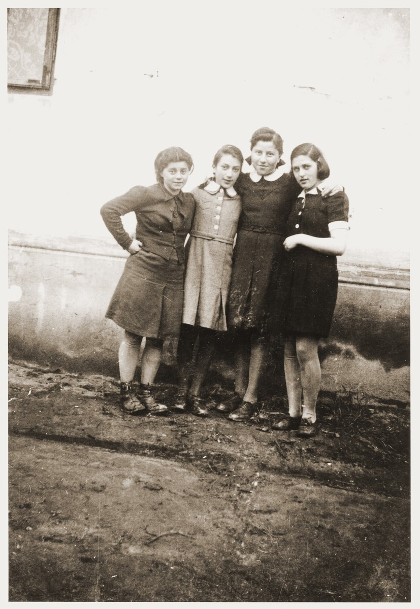 Four Jewish girls pose outside a building in the Zabno ghetto during a birthday party for their friend Hania Goldman.  Among those pictured are Rachela Goldman (second from the right).