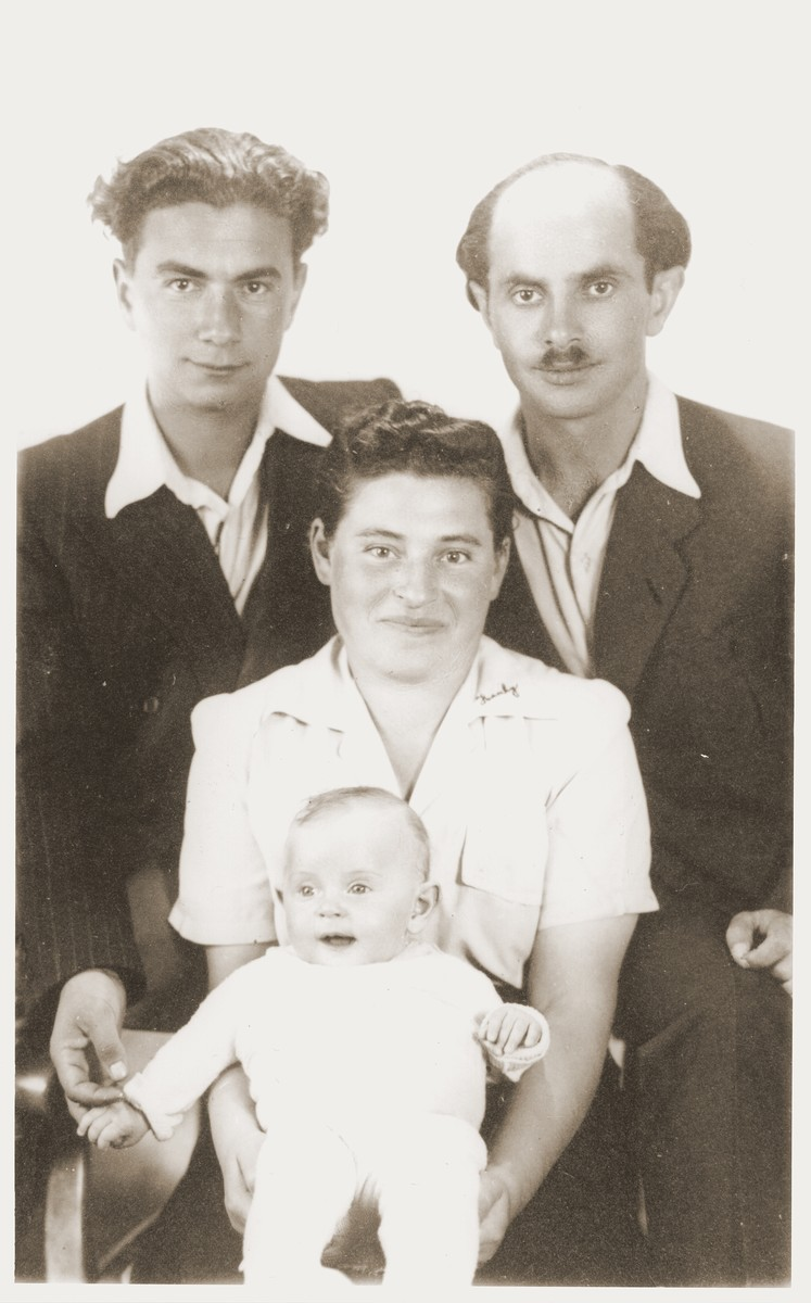 Studio portrait of the Miedzinski family at the Kibbutz Nili hachshara (Zionist collective) in Pleikershof, Germany.   Pictured are Noach and Sara (Feldberg) Miedzinski with their daughter Nili Ruchana, and their friend Baruch Chita (upper right).