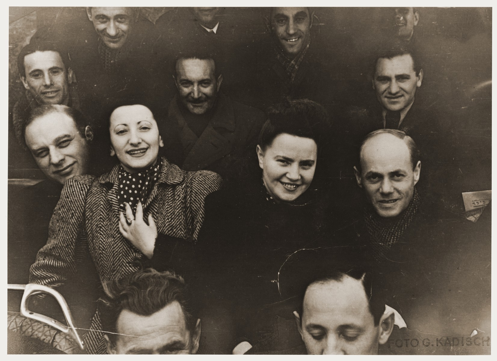 "Members of the X-Concentration Camp Orchestra on their bus during a concert tour.   Henia Durmashkin is on the left.  Her sister, Fania Durmashkin Becker is beside her.  Fania's husband, Max Becker is in the back, second from the right.  Henia Durmashkin was born in Vilna in 1926.  She is the daughter of Sonia and Akiva Durmashkin, who was a highly-regarded musician, composer, and the conductor of the choir in the City Temple of Vilna.  The youngest Durmashkin, Henia had a sister, Fania, a trained pianist, and a brother, Wolf, a child prodigy and later, a renowned conductor.  Henia's vocal talent was discovered early.  While in the second grade at the Tarbut Gymnasium, Henia performed songs for Hayyim Bialik at a program honoring his visit.  The songs were Bialik's poems put to music composed by Akiva Durmashkin.  Henia went on to study at the Conservatory of Music in Vilna, and in 1940, she was the only Jew accepted to the City Choir of Vilna.  In the summer of 1941, Henia and her family were moved into the Vilna Ghetto, and soon after, Akiva was arrested and deported during an action.  In 1942, the Hebrew Ghetto Choir of Vilna gave its first concert under the direction of Wolf Durmashkin with Henia and Fania both participating.  The Vilna Ghetto was liquidated in September 1943.  Sonia Durmashkin was too frail to be selected for labor.  Wolf was deported to labor camps in Estonia.  Henia and Fania were sent to Riga, and for the next two years, to a number of other labor camps.  In one camp, Henia met Abrasha Stupel, a violinist.  Henia and Fania were liberated on a death march from Dachau, May 1, 1945, by the U.S. Army.  Soon after, Henia was invited by Abrasha Stupel to join a group of musicians gathered at St. Ottilien DP Hospital.  They called themselves the ""St. Ottilien Orchestra,"" the ""X-Concentration Camp Orchestra,"" and finally the ""Representative Orchestra of the She'erit Ha-Peletah.""  In 1946, the orchestra relocated from St. Ottilien to Fuerstenfeldbruck.  They were employed by the JDC, UNRRA, and IRO to play at DP camps throughout the U.S. and British zones of Germany.  During her travels, Henia learned that her beloved brother, Wolf Durmashkin, had been killed along with other inmates of Klooga, one hour before the liberation of the camp.  In 1948, Leonard Bernstein traveled to Germany to conduct the Munich Symphony Orchestra.  In May, in a Munich theatre, he accompanied Henia for two Hebrew songs. Henia Durmashkin immigrated to the United States, where she and her sister, Fania, continued to perform."