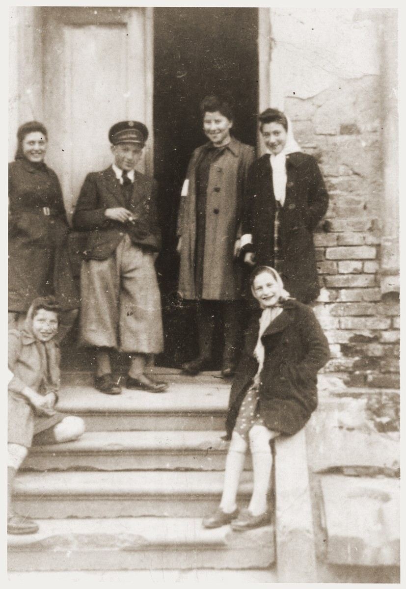 Hana Goldman (seated on the left) with a group of Jewish youth, wearing armbands, poses at the back entrance to the Goldmans' home in the Zabno ghetto.  Her sister Rachela is standing second from the right.