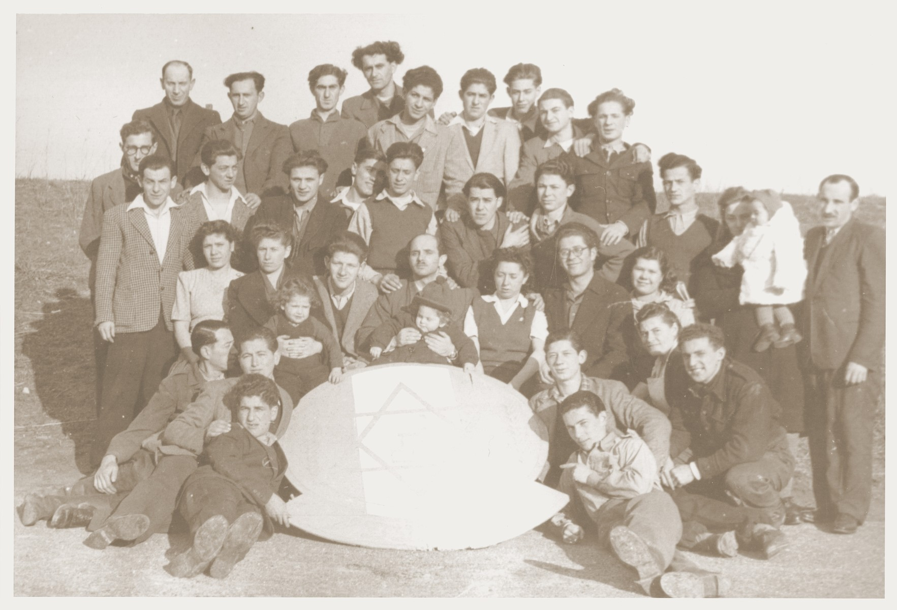 "Group portrait of the members of the Kibbutz Nili hachshara (Zionist collective) in Pleikershof, Germany, posing around a large plaque inscribed with a Star of David and the Hebrew word ""Nachem"" (comfort).    Seated in the center is Noach Miedzinski holding his daughter Nili.  On the far right is Aaron Charny standing next to his daughter."
