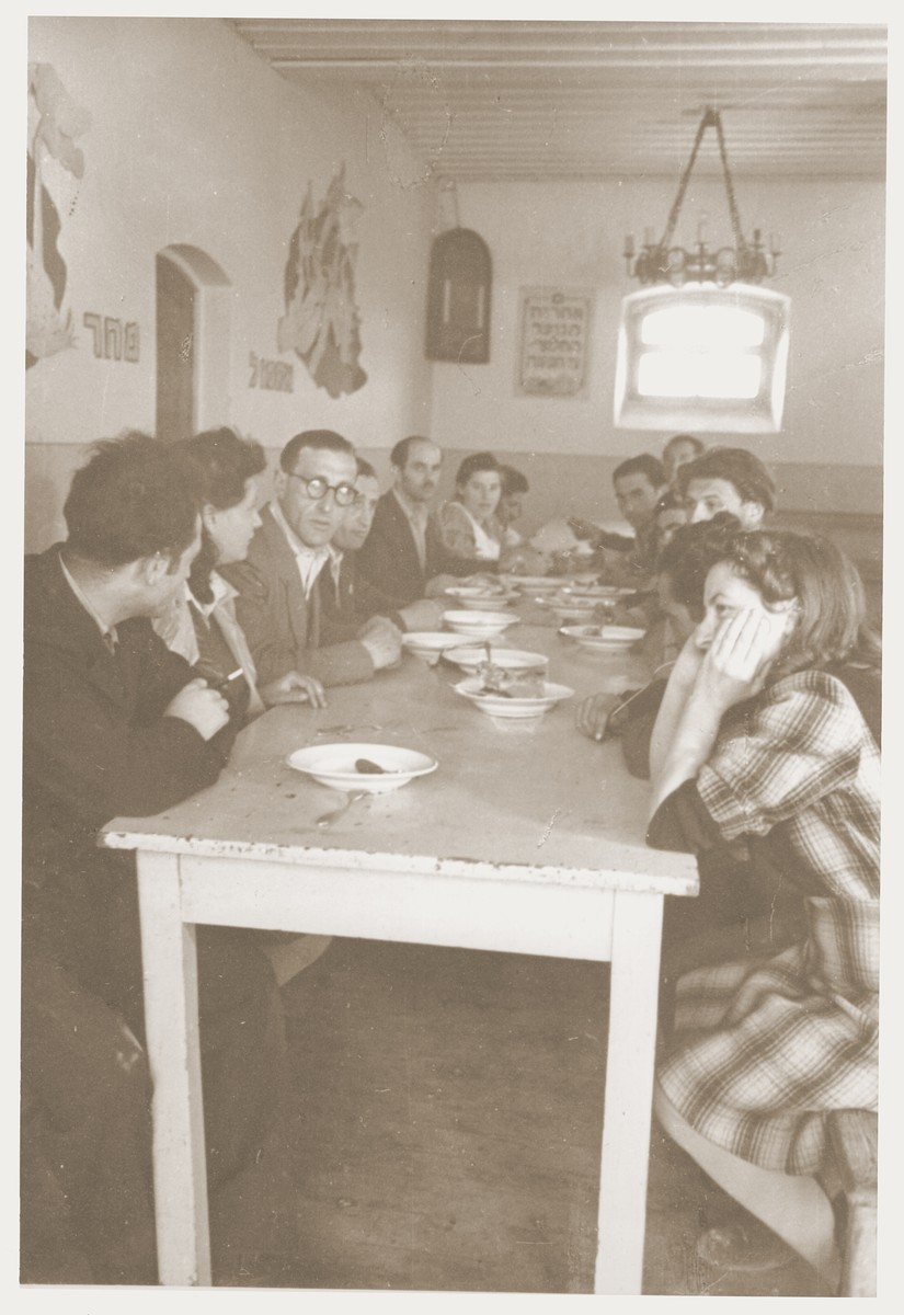Members of Kibbutz Nili hachshara (Zionist collective) in Pleikershof, Germany, sit around a table in the dining hall.