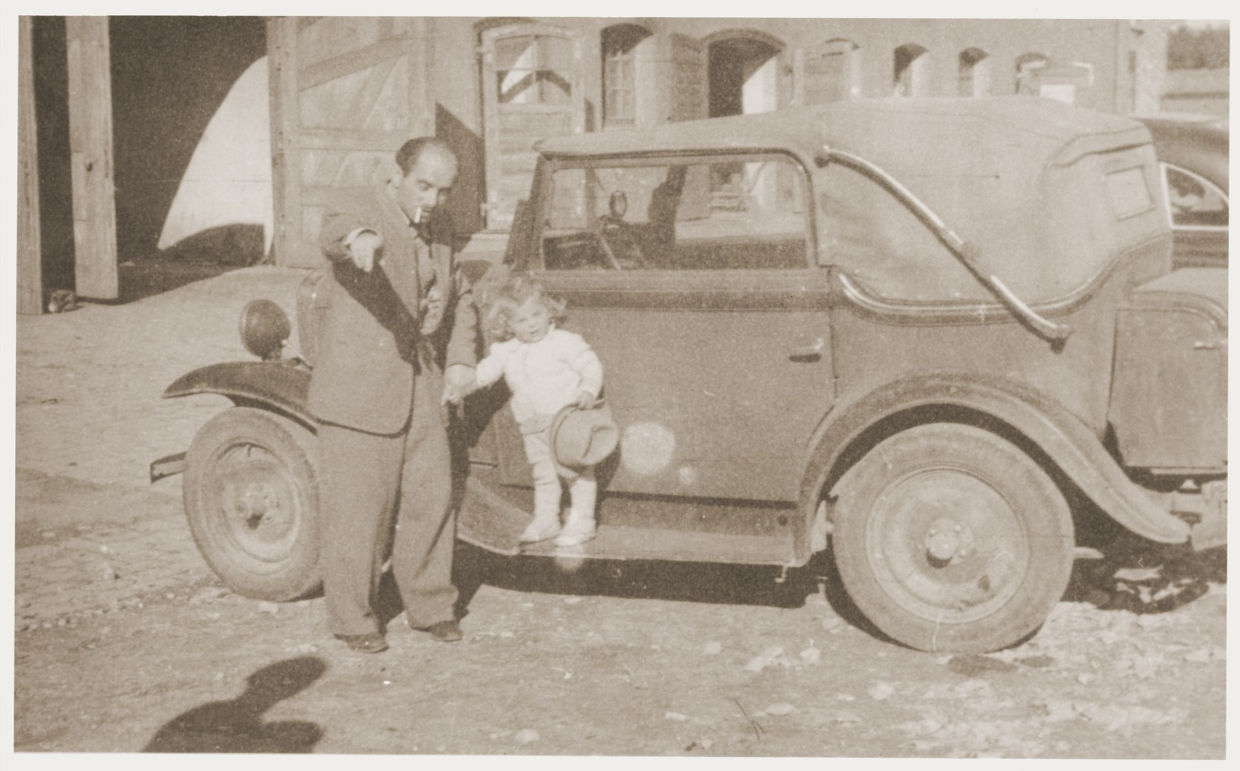 A little girl poses on the running board of a car while holding her father's hand at the Kibbutz Nili hachshara (Zionist collective) in Pleikershof, Germany.    Pictured are Noach Miedzinski and his daughter Nili Ruchana.