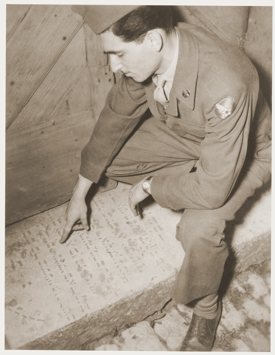 An American serviceman who is visiting the Kibbutz Nili hachshara (Zionist collective) in Pleikershof, Germany, reads a desecrated tombstone that had been used by Julius Streicher for a threshold to a building on his estate.