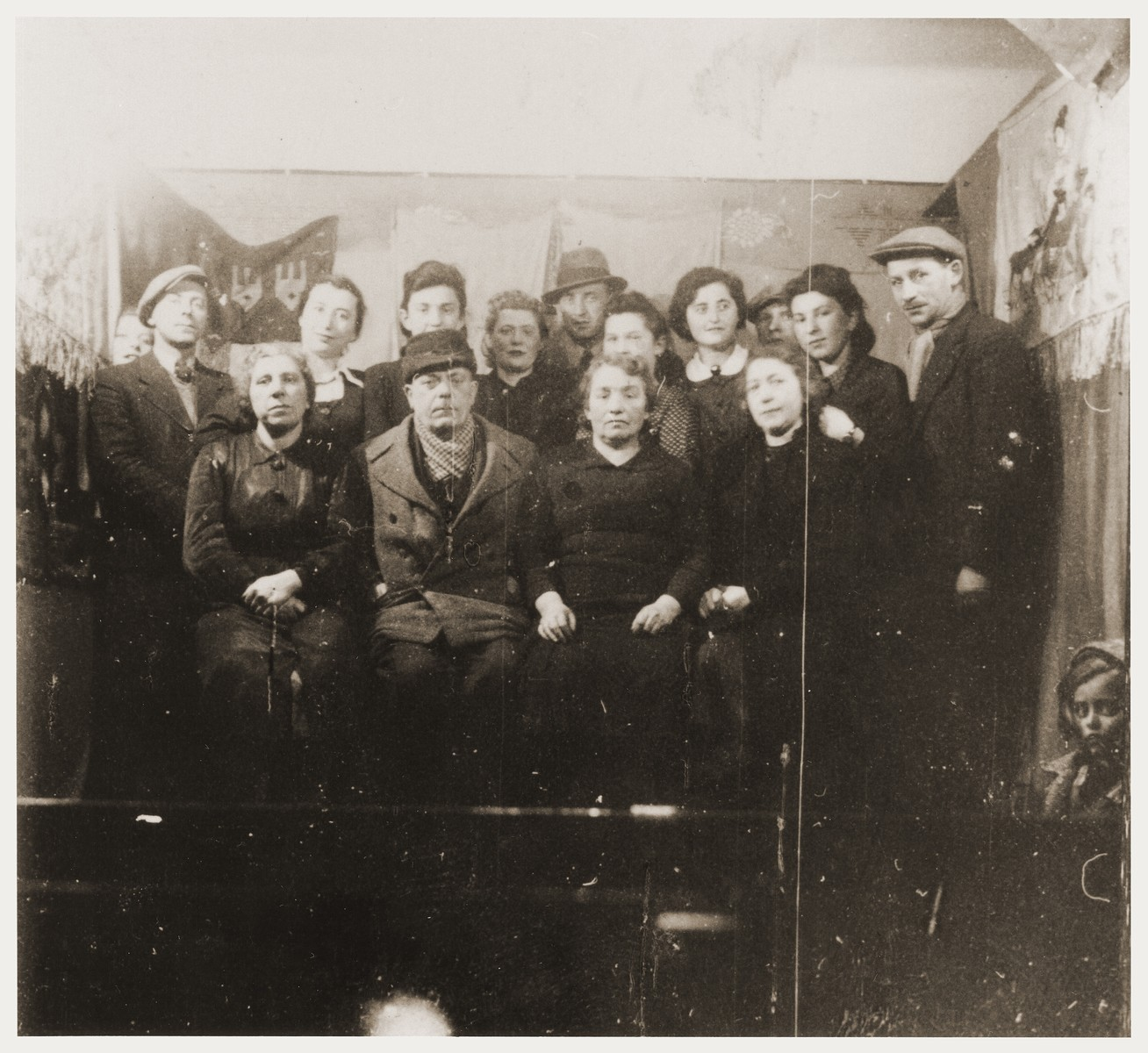 Group portrait of Jewish men and women in front of a stage set at a Purim celebration in the Zabno ghetto.
