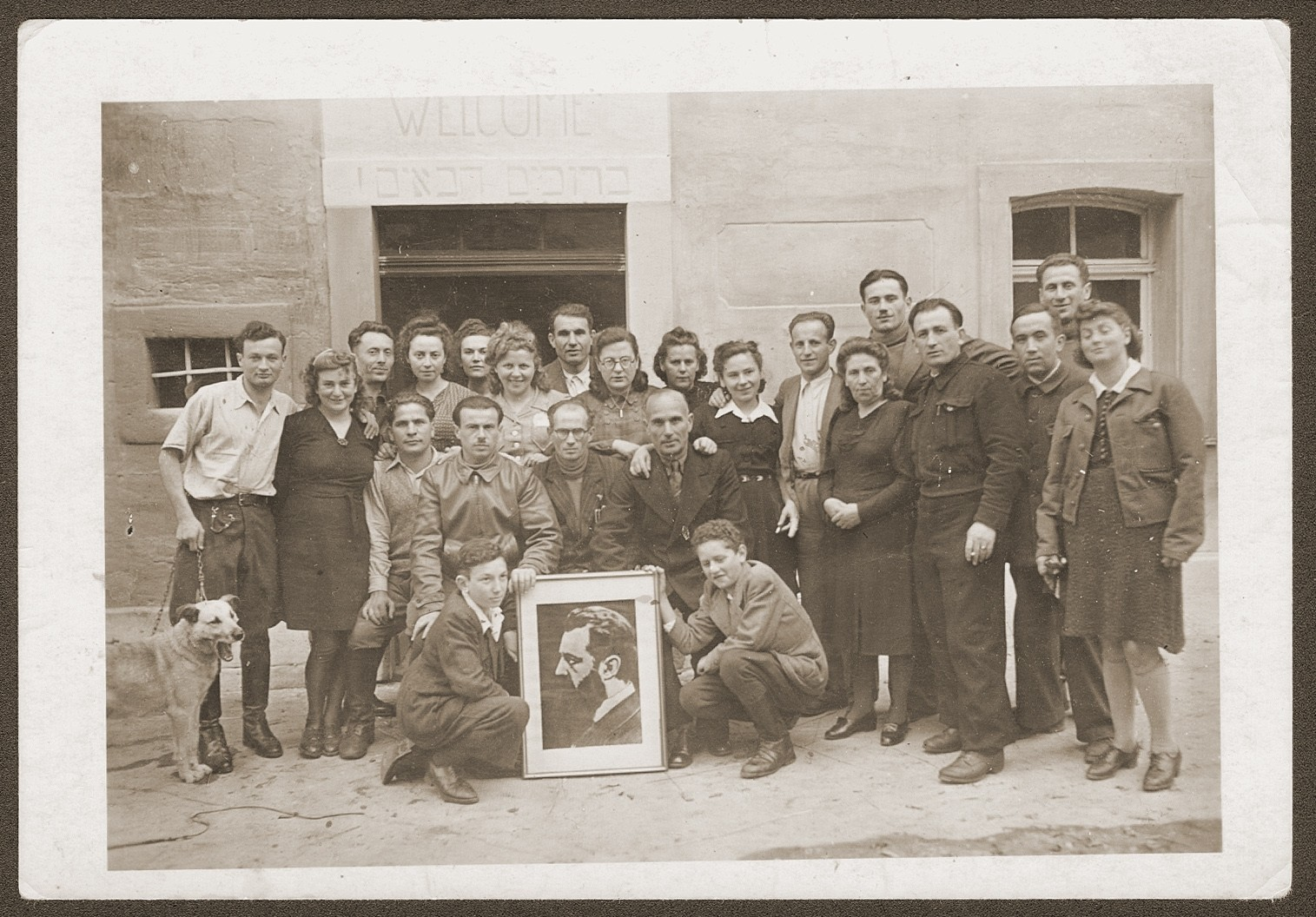 Group portrait of members of the Zettlitz hachshara with a framed picture of Theodor Herzl.
