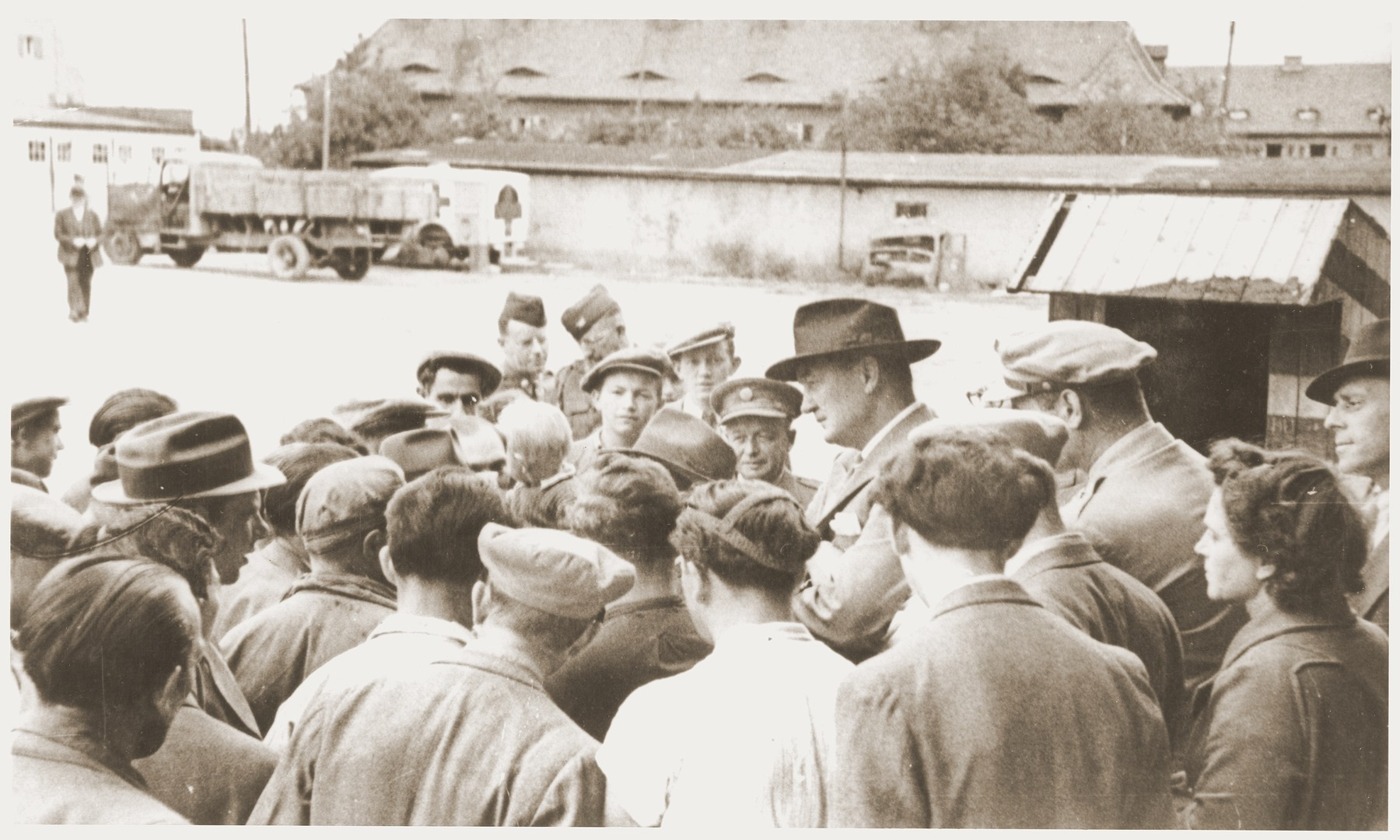 Members of the Kibbutz Nili hachshara (Zionist collective) in Pleikershof, Germany crowd around an American official and his entourage during a tour of the settlement.