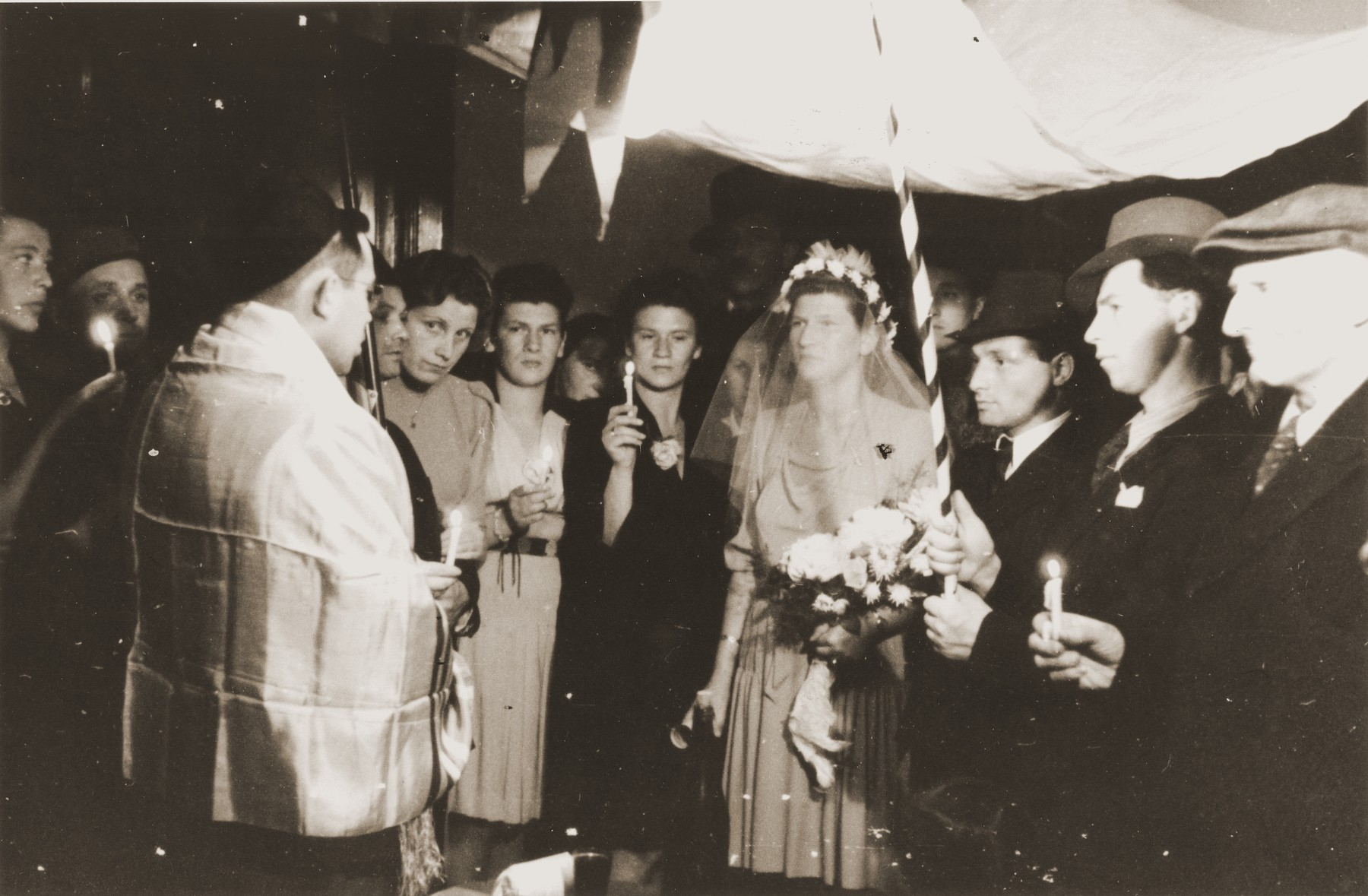 American military chaplain Rabbi Lifschitz officiates at the wedding of two members of the Bricha organization held at Frankgasse 2..    The bride is Greta Zandberg.