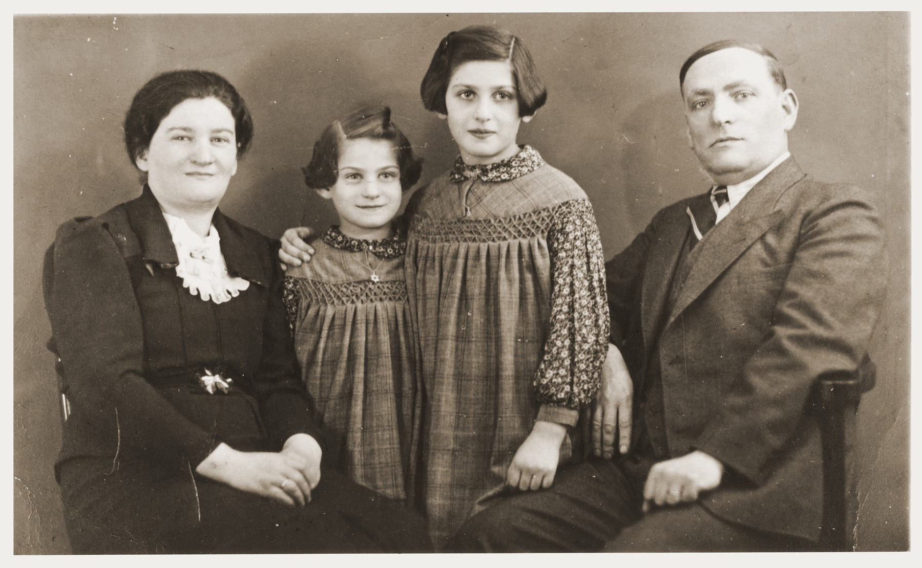 Studio portrait of a family of German Jews of Polish origin, who were forced to return to Poland in 1938.  The family lived for a time in Zabno with the Goldman family.