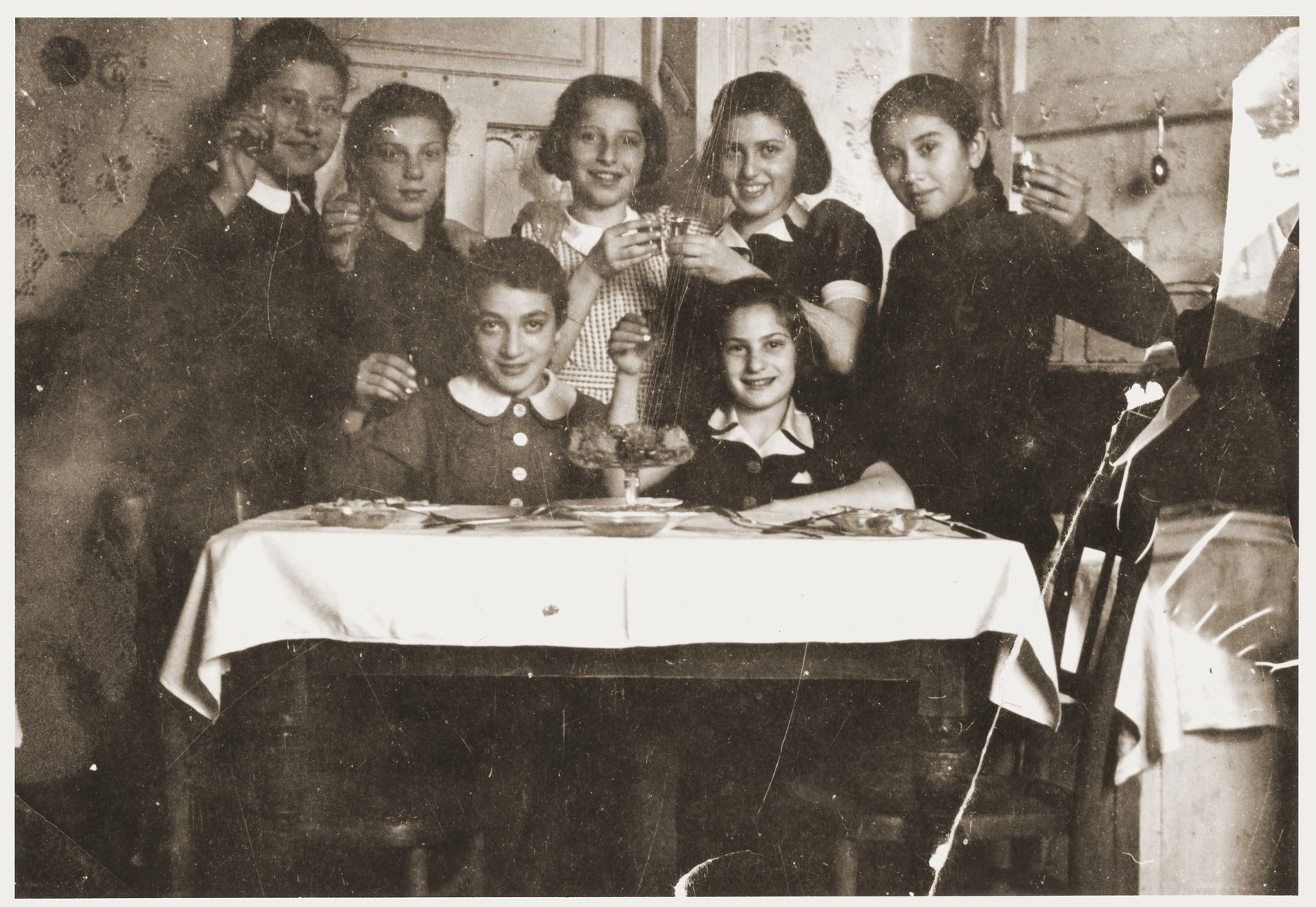 A group of Jewish girls in the Zabno ghetto toast their friend on her twelfth birthday.    Pictured are Hania Goldman (the birthday girl, standing in the middle), and her sister, Rachela (standing on the left).