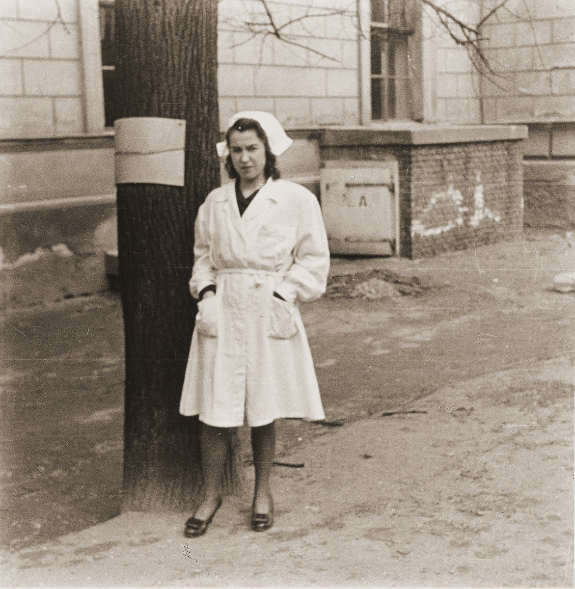 Celia Chaiken-Wells, a nurse and relief worker at the Rothschild Hospital poses in front of the building.  .   George Birman was born in 1922 in the German city of Konigsberg, and grew up near the Baltic port of Klaipeda in Lithuania.  His father, Abel Birman, gave him a Voigtlander camera as a present for his tenth birthday with which he took pictures of pre-war, wartime and postwar Europe.  In 1941 Birman was imprisoned in the Kovno ghetto and then was sent to a number of slave labor camps.  He managed though to keep his photographs with him.  On the night of July 9, 1944, before escaping from the Kedainiai labor camp outside of Kovno, Birman handed over his passport, birth certificate and approximately 150 photographs and negatives to his father.  As the camp cook, his father wrapped the documents in waxed paper and buried them in a canister under the kitchen.  Birman cut the barbwire fence surrounding the camp with pliers.  Along with his father and a companion, he crawled through a drainage ditch and hid in a tall rye field before running away to the forests.  One month later, after the German retreat, Birman dug up his photographs -- which he found undamaged -- and photographed the places where he had worked and escaped.  In postwar Vienna, Birman studied engineering and worked for Bricha, the illegal organization that smuggled survivors to Palestine.  He guided refugees to the Rothschild Hospital and from there on routes to Palestine.  He lived off and on at the Rothschild Hospital for four years registering refugees while his father helped manage the hospital's supplies.