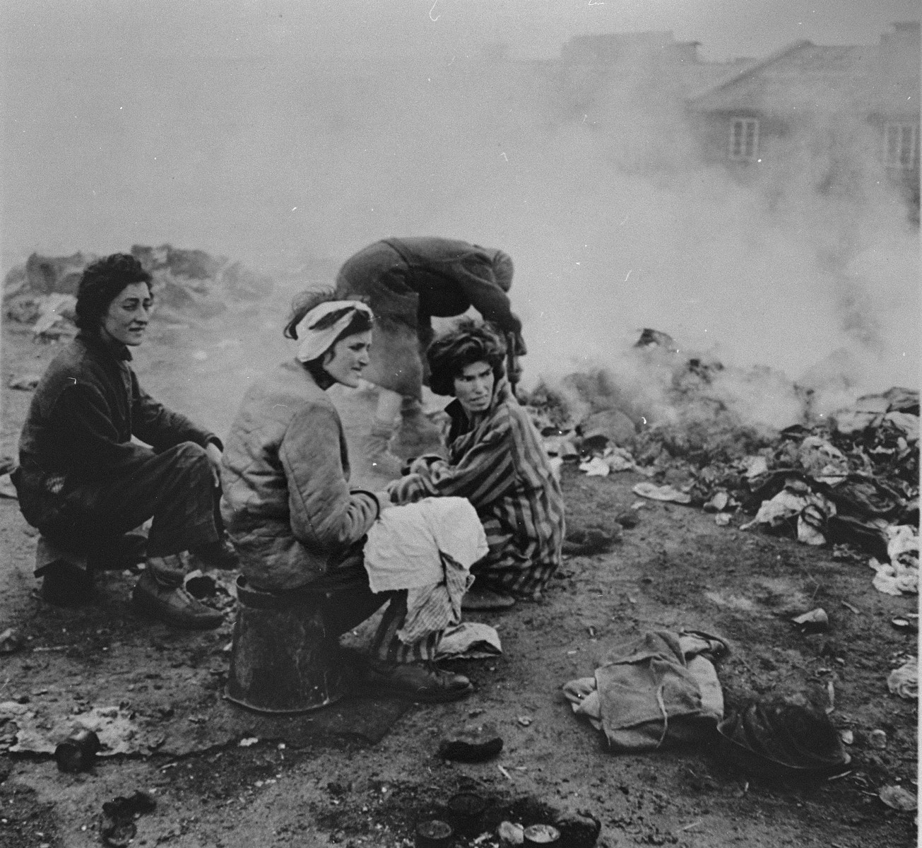 Survivors in Bergen-Belsen sit amongst clothing that is  being burned to control an outbreak of typhus.