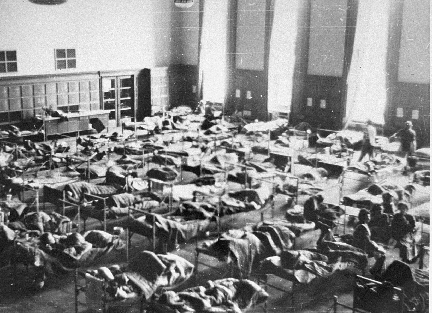 Bergen-Belsen survivors are treated in an improvised hospital set up with hundreds of beds in the Rundhaus, the former headquarters of the German Army in Bergen-Belsen.