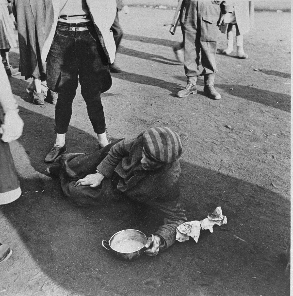 A survivor in Bergen-Belsen, who is too weak to stand, lies on the ground holding a soup bowl.
