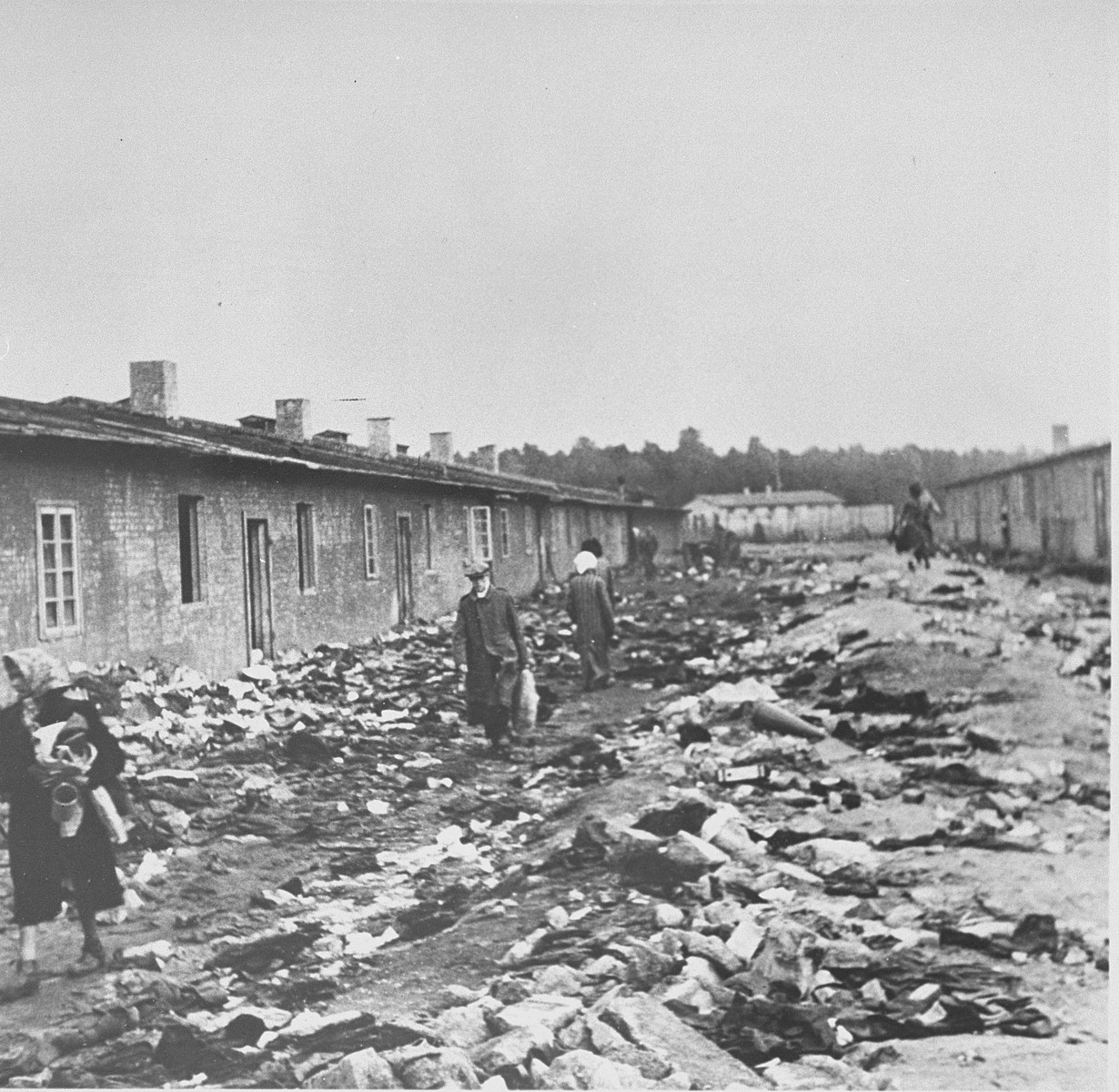 Survivors walk on refuse filled streets in Bergen-Belsen concentration camp after its liberation by the British Army.