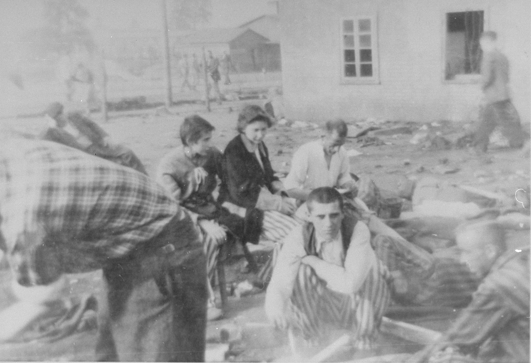 Survivors in Bergen-Belsen rest outside a barrack.