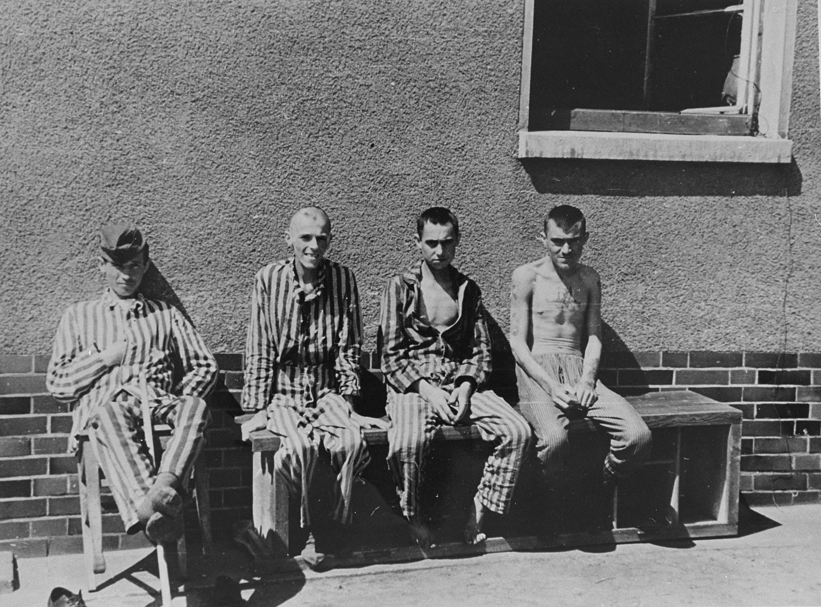 Survivors sit on a bench outside of a camp building in Bergen-Belsen.