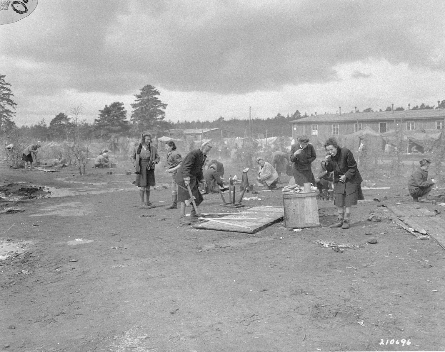 "Survivors in Bergen-Belsen tend to chores after their liberation.  The original caption reads: ""Women political prisoners, freed by advancing allied armies at their German prison camp at Belson [sic], Germany, wash their teeth with utensils supplied them by their liberators.  Woman at left is chopping up a door for fire wood.  Camp is now operated by British 2nd Army."""