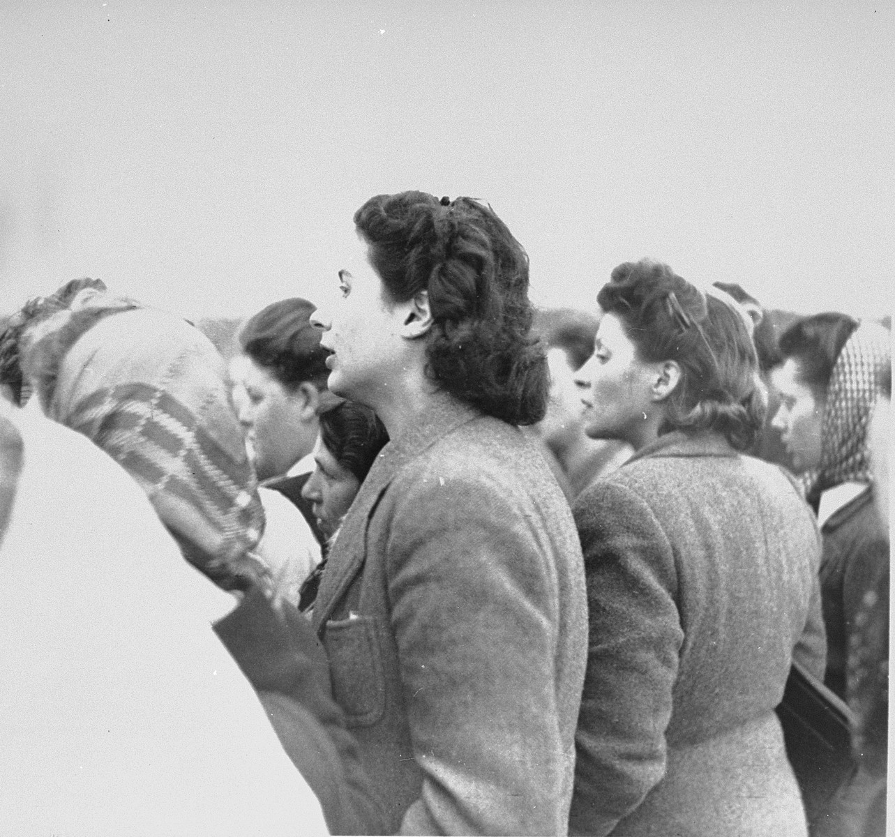 Women survivors in Bergen-Belsen watch British troops forcing former SS guards to bury corpses in a mass grave.