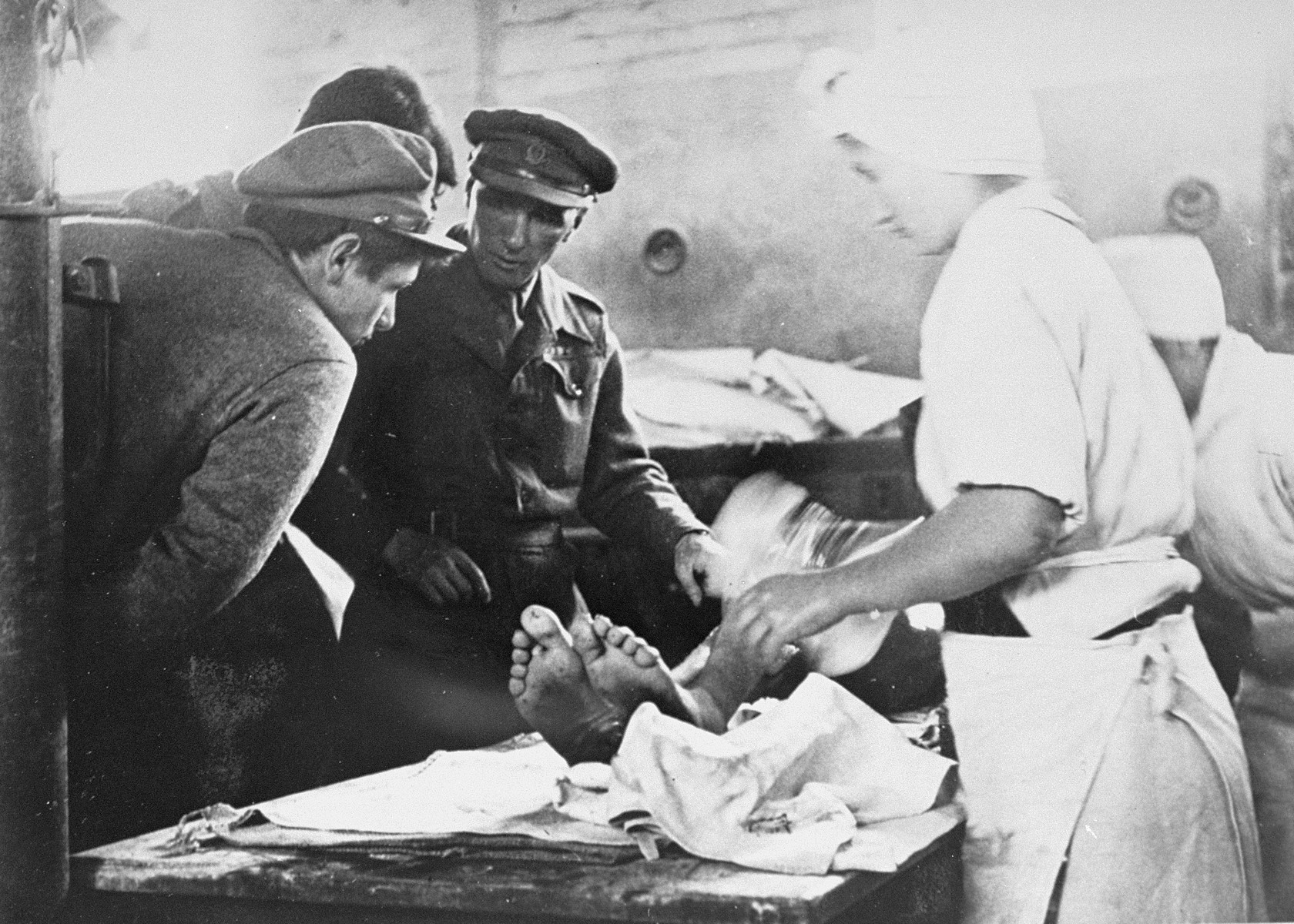 British physicians examines a Typhus patient who is being bathed by nurses.