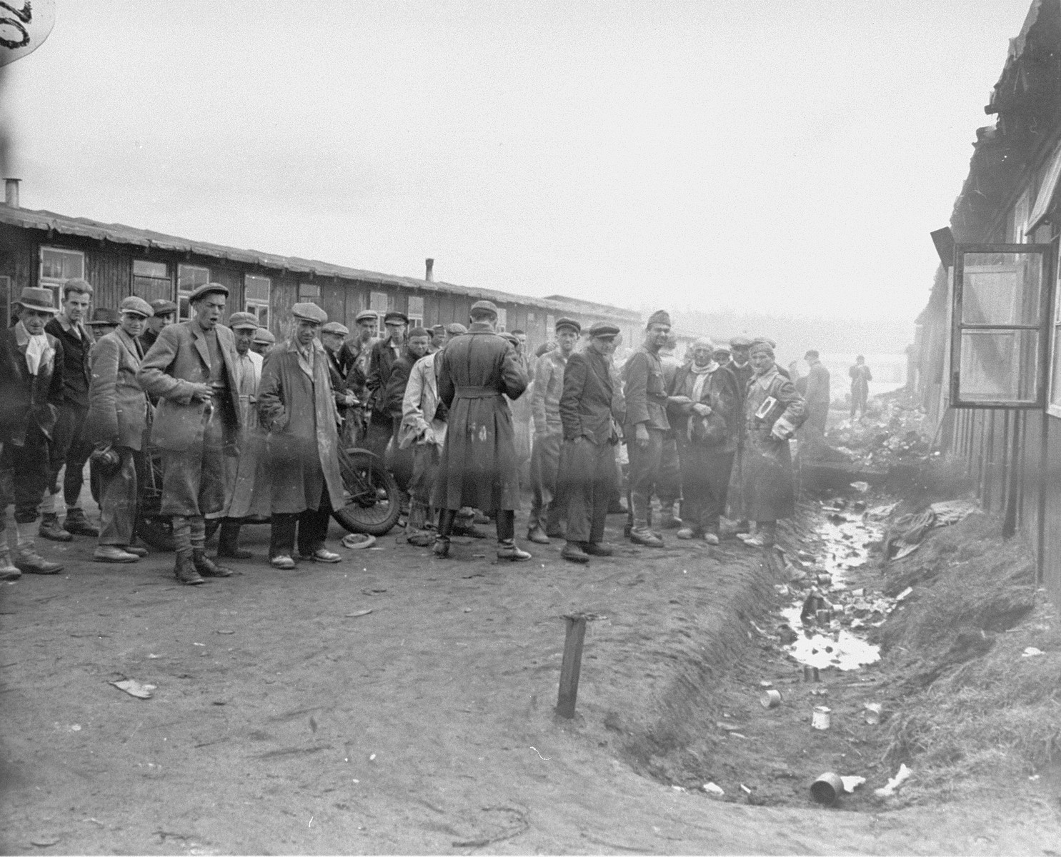 Unidentified soldiers dusting survivors in Bergen Belsen with DDT powder to halt the spread of Typhus.
