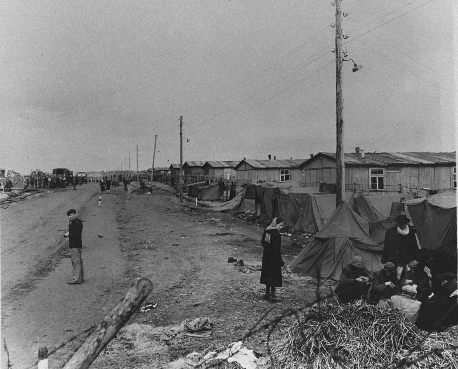 View of the main street in the Bergen-Belsen concentration camp (looking toward the entrance) lined with a row of small tents that have been pitched outside the barracks.    In the foreground, a group of survivors huddles in front of one of the tents, while, in the distance, other liberated prisoners walk along the unpaved road.   Original caption is illegible.