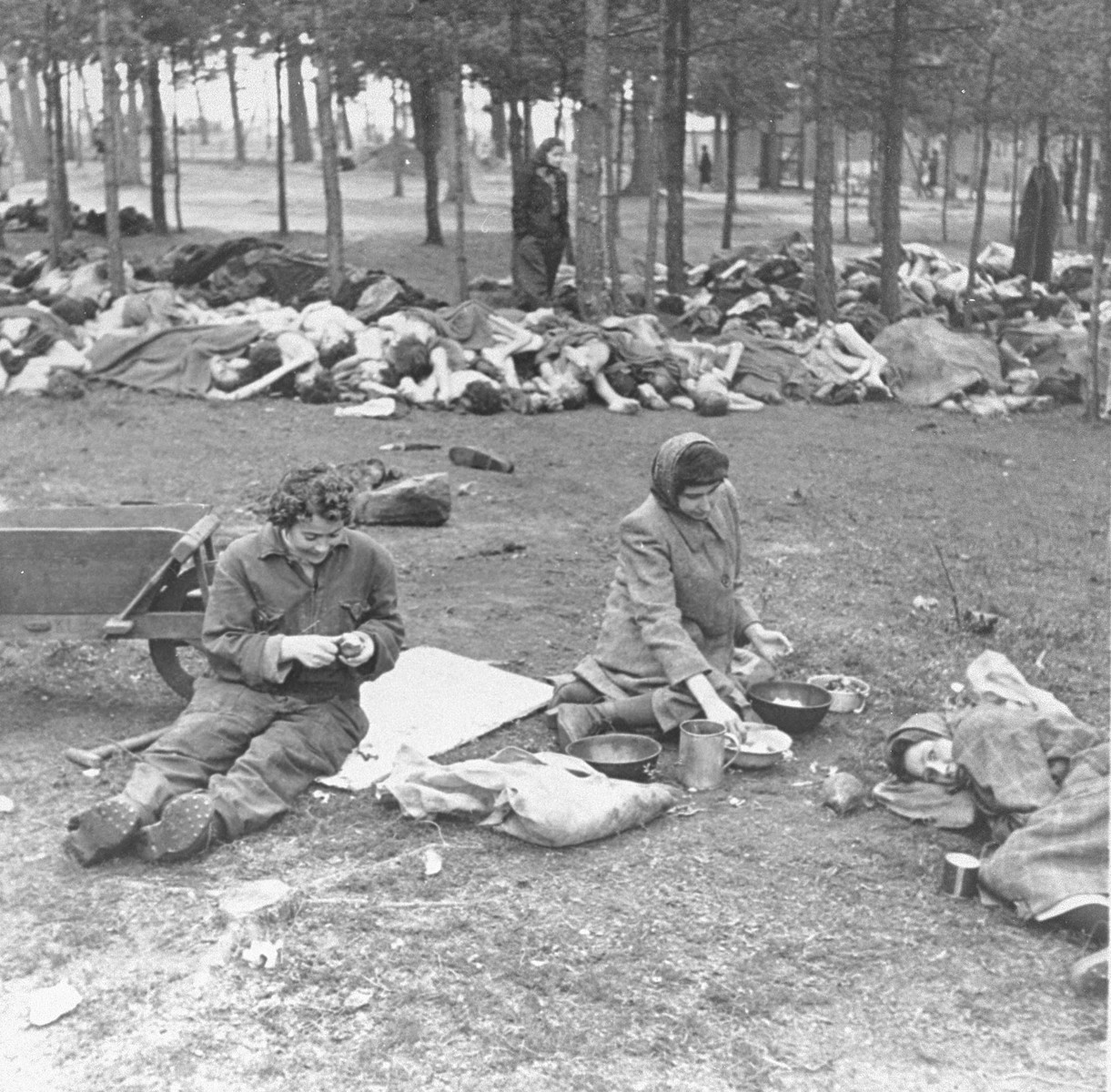"""Survivors in Bergen-Belsen peel potatoes while behind them lie the corpses of prisoners who died before the liberation of the camp.  The original caption reads: """"Women peeling potatoes in front of piles of dead bodies."""""""